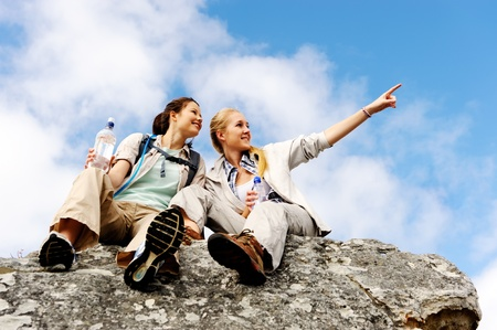 rambling: two women take a break from trekking and rest on a rock outdoors