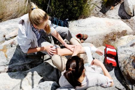 botiquin de primeros auxilios: Una mujer ha torcido el tobillo durante una excursión, su amigo utiliza el kit de primeros auxilios para atender a la lesión