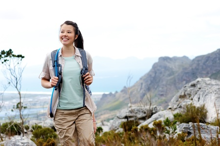 Carefree brunette girl walks outdoors hiking and exploring. she is cheerful and happy Stock Photo - 11900332