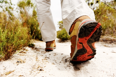 step fitness: person hiking outdoors, boot on sandly pathway in the wilderness. trekking