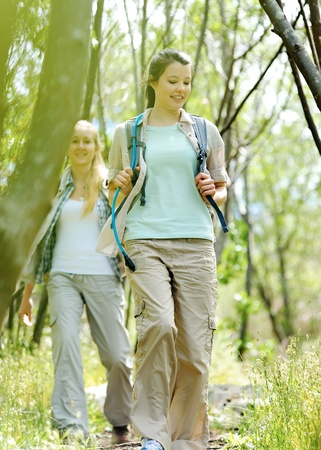 Women walking outdoor in the woods, happy exploring and adventure lies ahead for these wilderness trekking friends photo