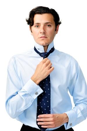 vistiendose: Hombre de negocios se concentra en el ajuste de su corbata, aislado en blanco