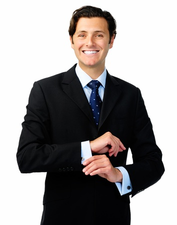 Smiling confident business man in a formal suit adjusts his cufflinks photo