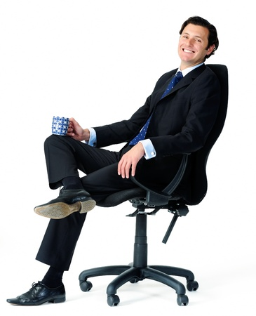 people sitting on chair: Male office worker relaxes on a chair, enjoying a cup of coffee