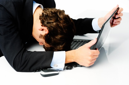 Businessman in suit puts his head down on his laptop computer when he fails to meet his target photo