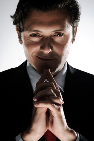 Dramatische Beleuchtung macht den Geschäftsmann im Anzug bedrohlich aussehen