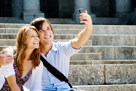 photographing: couple take a picture together while visiting a tourist attraction, smiling and having fun