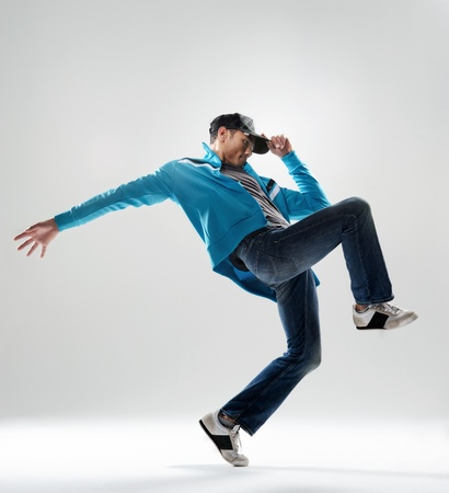 hip hop pose: modern hip hop dancer lifts his leg and does some moves while dressed in trendy modern clothing Stock Photo