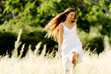 outstretched: beautiful carefree woman skips and plays outside, cheerful and smiling