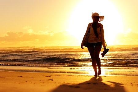flops: woman walking on the beach at sunset Stock Photo