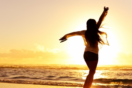 carefree woman dancing in the sunset on the beach. vacation vitality healthy living concept