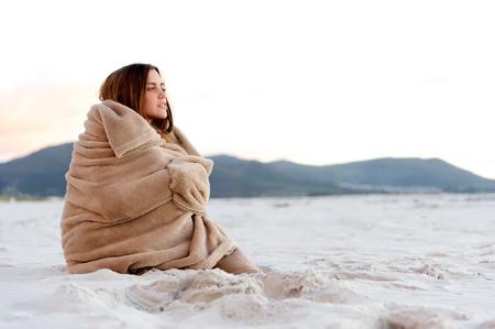 resfriado: mujer fr�a envuelve una manta sobre su cuerpo mientras se est� sentado en la playa despu�s del atardecer.
