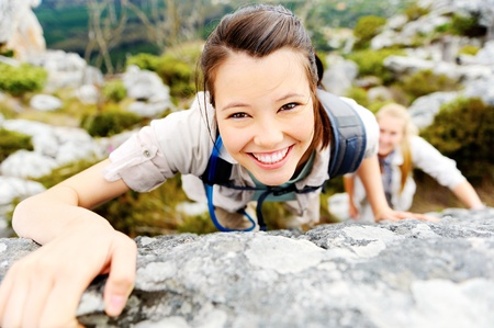 happy carefree hiking backpacker climbs a rock outdoors while leading a healthy lifestyle photo