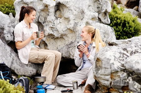 two camping women sitting together enjoying a nice hot drink photo