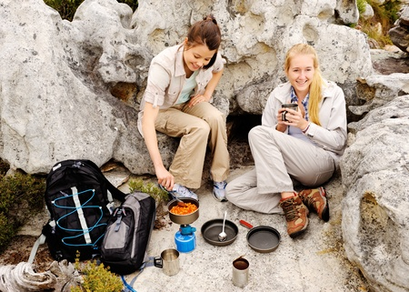 backpackers: two friendly women cook up some food while camping in the wilderness. outdoor hiking lifestyle concept Stock Photo
