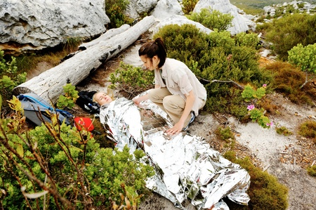 injured woman: A woman is injured while hiking outdoors. her friend has covered her with and emergency blanket and checks on her using a first aid kit