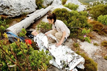 lesionado: Una mujer se lesiona mientras está al aire libre, senderismo. su amiga la ha cubierto con una manta y de emergencia y los controles sobre su uso de un botiquín de primeros auxilios