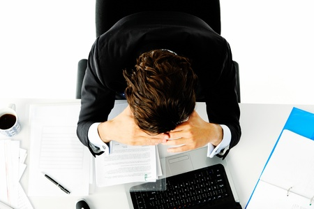 Businessman in suit puts his face in his hands when he is overwhelmed with too much work Stock Photo - 11900291