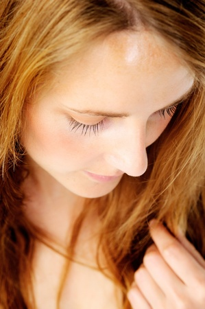 top down: Close up portrait of a shy redhead caucasian woman looking down, with barely any make up - a top down perspective