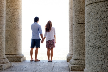Couple hold hands and looks out into the bright sunshine photo