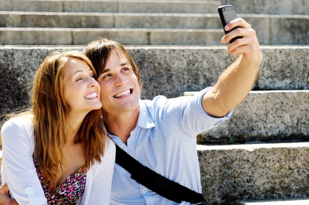 Man uses his smartphone camera to snap a picture of him and his girlfriend on honeymoon photo
