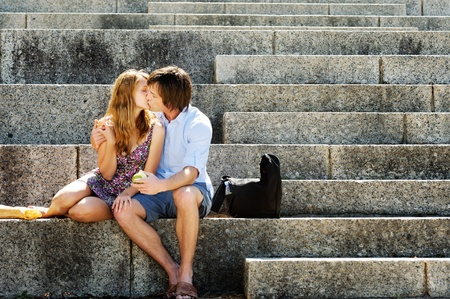 romantic kiss: A couple traveling sit on the steps of a local landmark and kiss in the afternoon sunlight