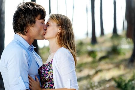 enamorados besandose: Los amantes abrazados y compartiendo un beso al aire libre