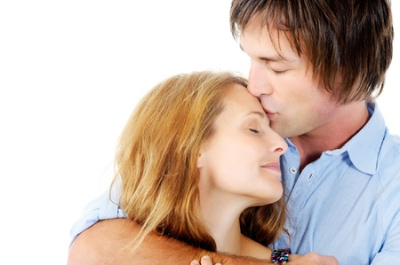 contented: Handsome man kisses loving girlfriend on her forehead, isolated on white Stock Photo
