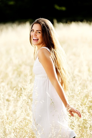 freedom leisure activity: gorgeous girl walking in the field of long grass and dragginhg her hand touching the dry grass while laughing and smiling, carefree healthy lifestyle