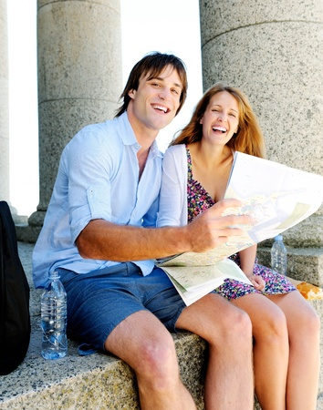 couple hold map and smile towards camera while sitting at an old tourist attraction. young travel concept photo