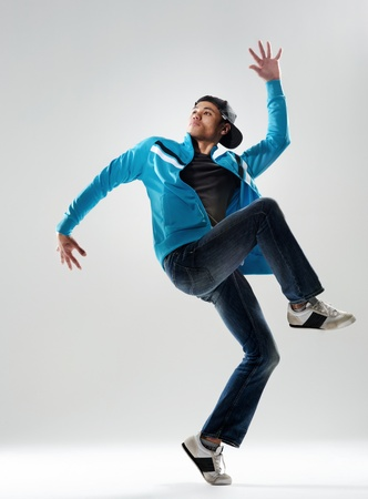 modern hip hop dancer lifts his leg and does some moves while dressed in trendy modern clothing photo