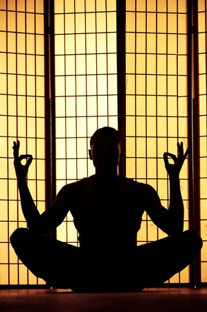 meditation room: Silhouette of a man meditating and finding a zen moment