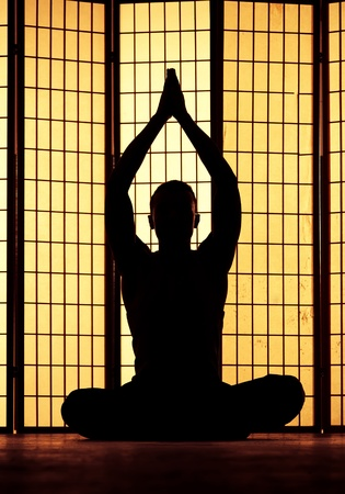 Silhouette of a man meditating and finding a zen moment photo