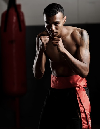Martial arts fighter stands in a defensive stance and stares ahead ready to embrace conflict photo