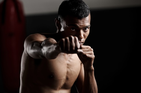 dramatic lighting on a martial arts fighter punching in the gym Stock Photo - 12346794