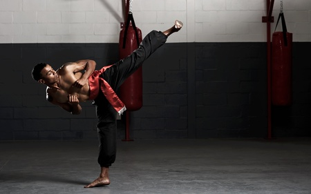 kung fu: Kung fu student practises his kicks in the gym, training for a fight