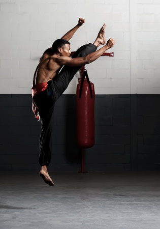 Kung fu student practises his kicks in the gym, training for a fight photo
