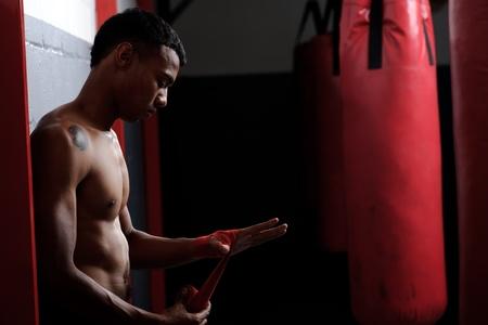 nackte brust: Kämpfer bereitet für die Ausbildung durch Umwickeln der Hand mit Schutzstreifen