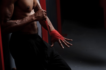 asian abs: Fighter prepares for training by wrapping his hand with protective tape Stock Photo