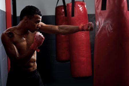 kickboxing: action of a boxing martial arts fighter training on a punching bag in the gym