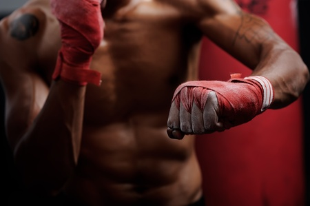 punching: action of a boxing martial arts fighter training on a punching bag in the gym