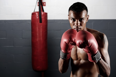 punching bag: portrait of a confident young boxer in the gym Stock Photo