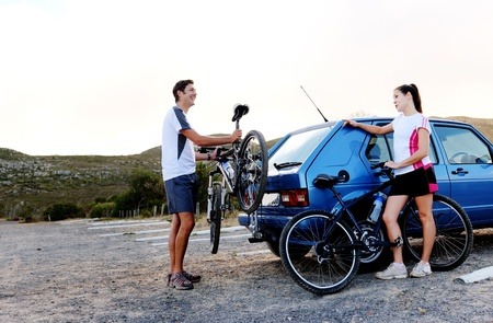 Panorama of a couple who have finished mountain biking outdoors and are loading the bicycles onto the car bike rack. large image, lots of copyspace, healthy lifestyle scene. photo