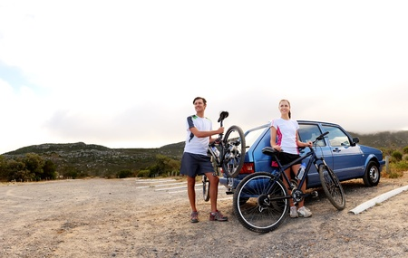 car lots: Panorama of a couple who have finished mountain biking outdoors and are loading the bicycles onto the car bike rack. large image, lots of copyspace, healthy lifestyle scene. Stock Photo