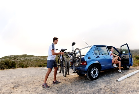 Panorama of a couple who have finished mountain biking outdoors and are loading the bicycles onto the car bike rack. large image, lots of copyspace, healthy lifestyle scene. Stock Photo