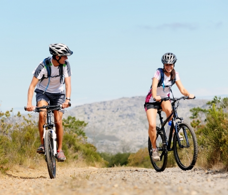 mountain bicycles: Happy carefree mountain bike couple cycling outdoors and leading a healthy lifestyle.  Stock Photo