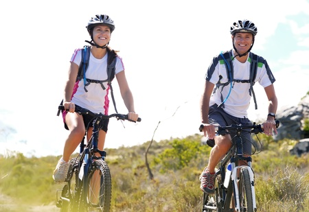 Happy carefree mountain bike couple cycling outdoors and leading a healthy lifestyle.  Stock Photo