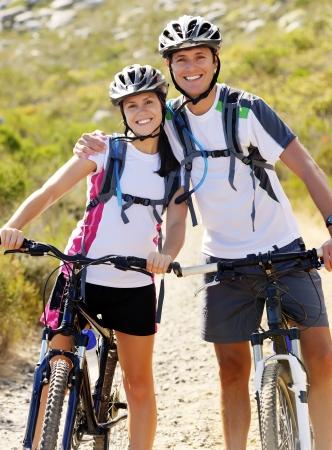 andando en bicicleta: Feliz despreocupados en bicicleta de monta�a al aire libre, un par de ciclismo y llevar una vida sana.