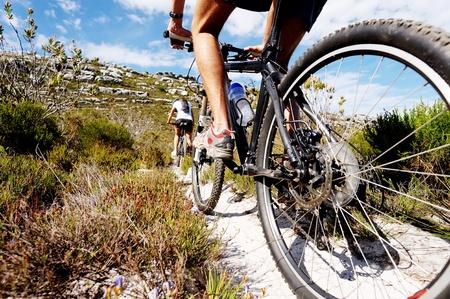 ciclismo: Vista granangular de un ciclista en bicicleta en un sendero natural en las montañas. dos personas que viven un estilo de vida saludable Foto de archivo