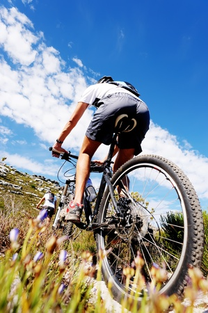 Wide angle view of a cyclist riding a bike on a nature trail in the mountains. two people living a healthy lifestyle  photo